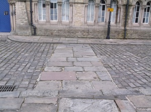 The wide flat paving shows the line of one of the substantial tower house walls